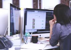 woman looking at two computer screens
